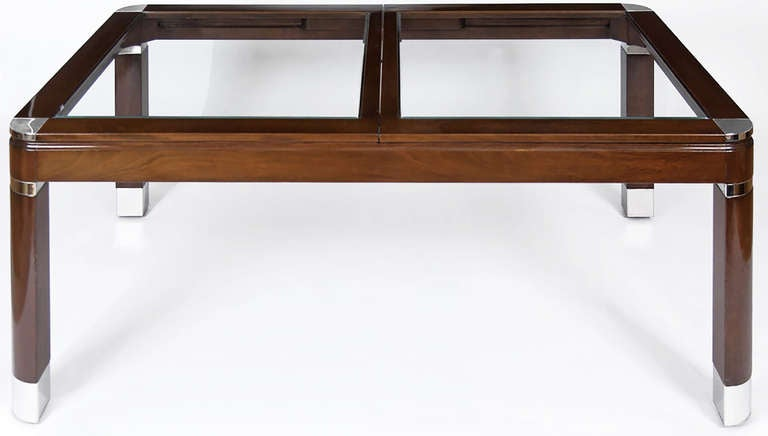 Superb dining table made of mahogany and glass, accented by chrome sabots, banding, and corners. With two leaves.
