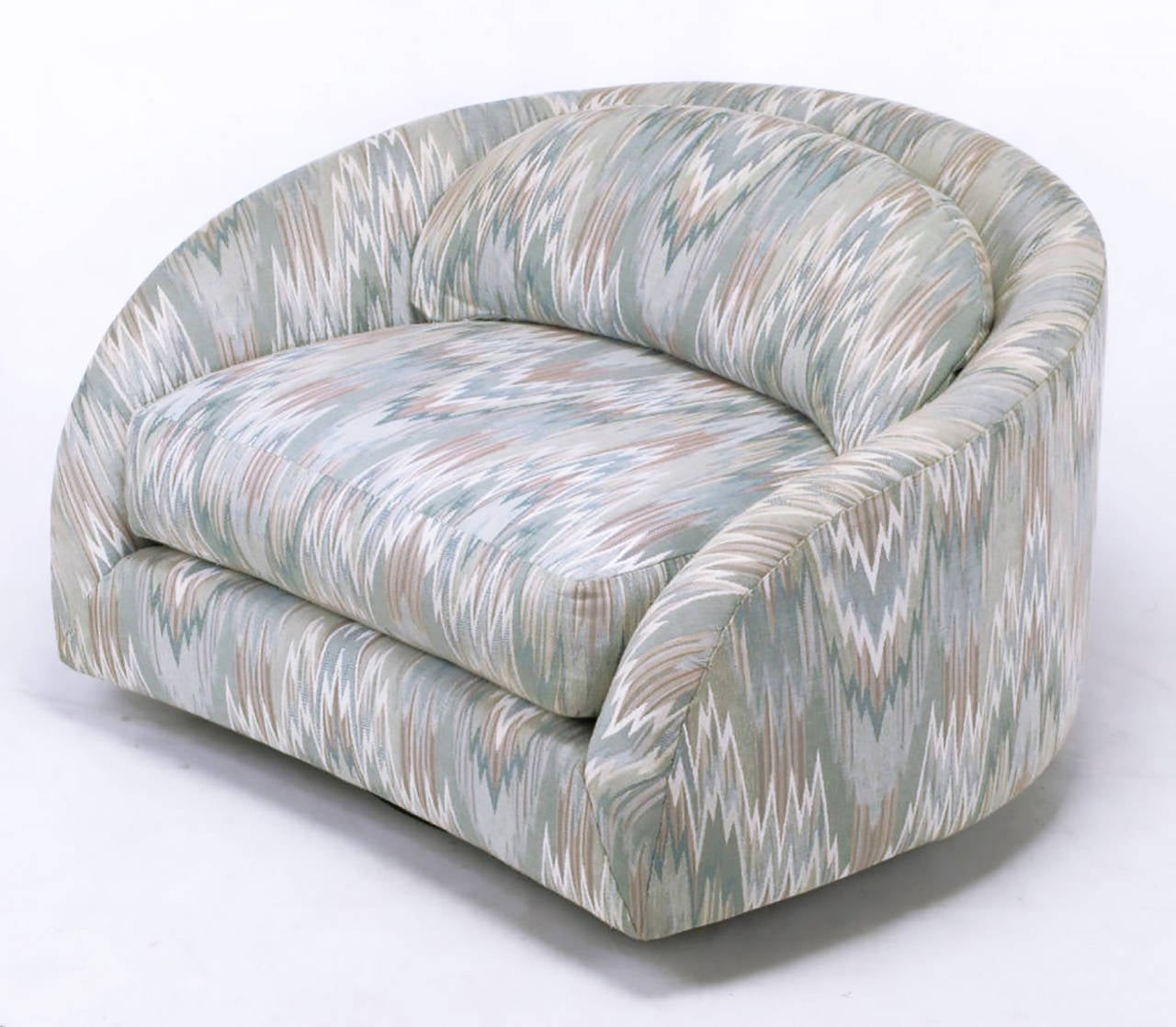 Swiveling barrel back club chair in a periwinkle blue and rose flame stich upholstery. Low slung and extremely comfortable with wide, loose cushions.