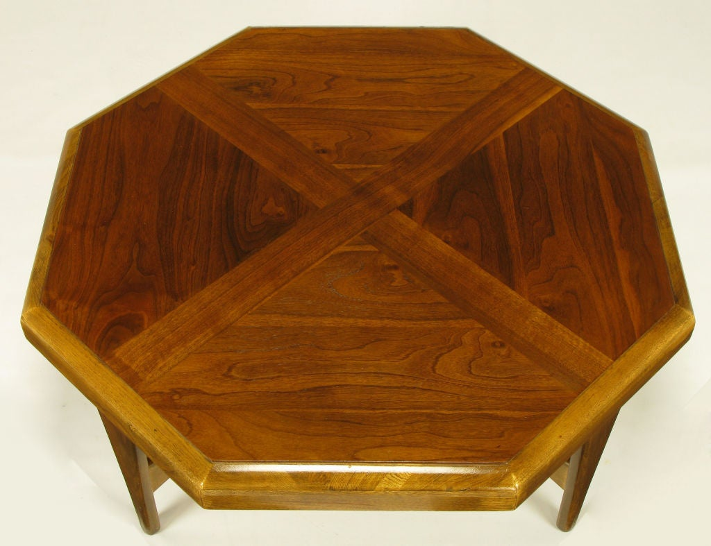Octagonal coffee table with radius edging and figured walnut parquetry top with X-pattern that is carried through to the bottom paddle end X-stretcher. Superior build quality with burned in style and serial numbers to the underside of the top.