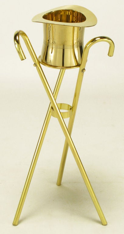 Unique and inspired champagne cooler or ice bucket on three canes in tripodal form stand. Solid brass top hat and brass plated canes.