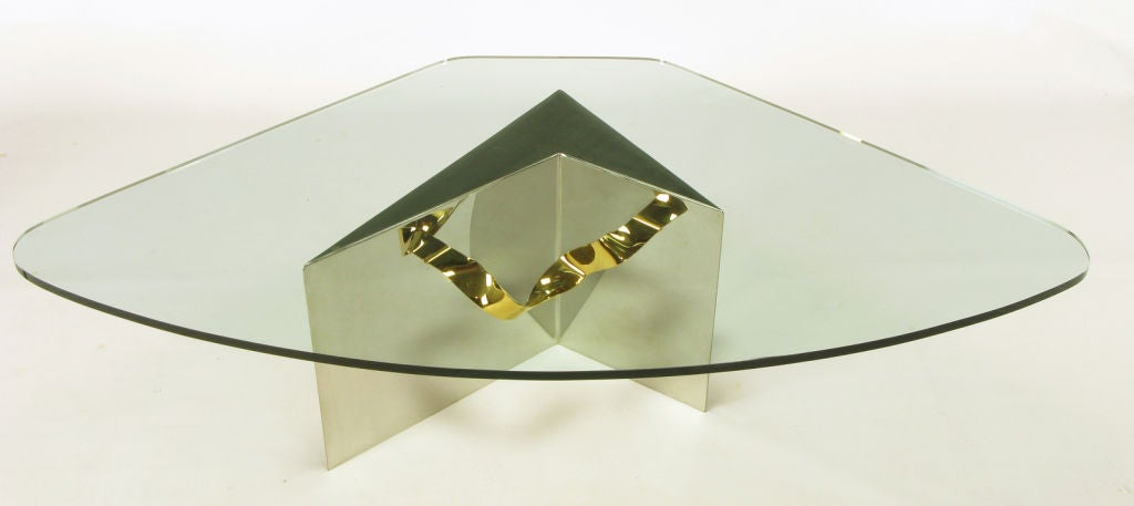 A bit of a Postmodern design, this table features a highly polished stainless steel chevron-form base, with brass ribbon appearing to run through it. Fitted glass top.