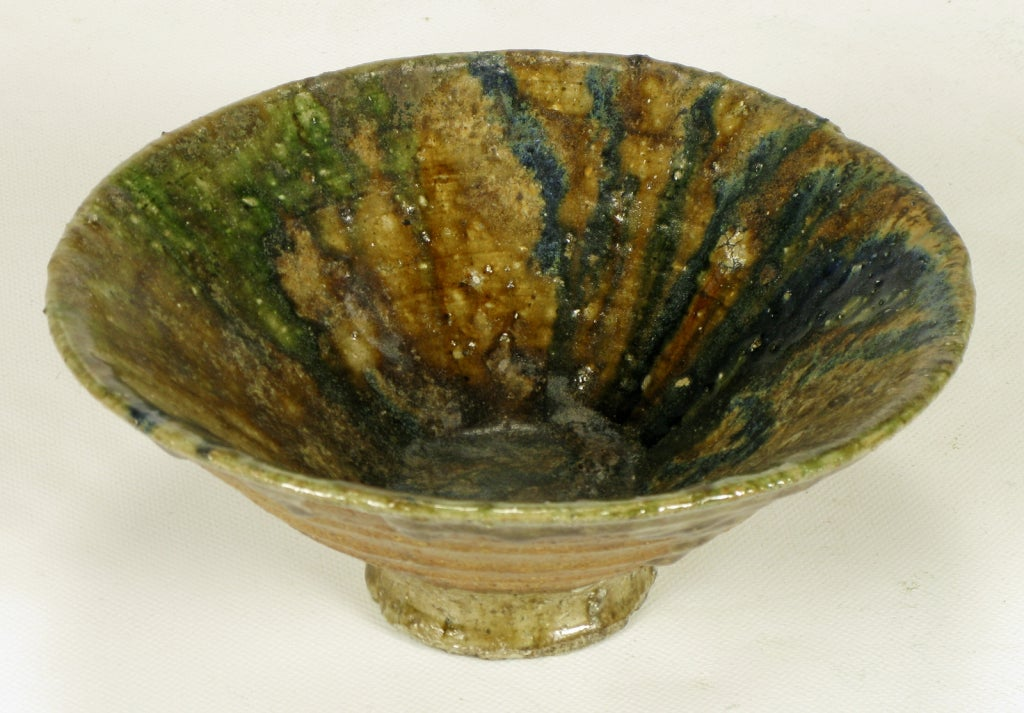 Hand thrown and glazed terra cotta bowl; ribbed and footed. Blue and green drip glazed interior and partial exterior.  From the collection of William Hoffman, a professor of ceramics at the Art Institute of Chicago.
