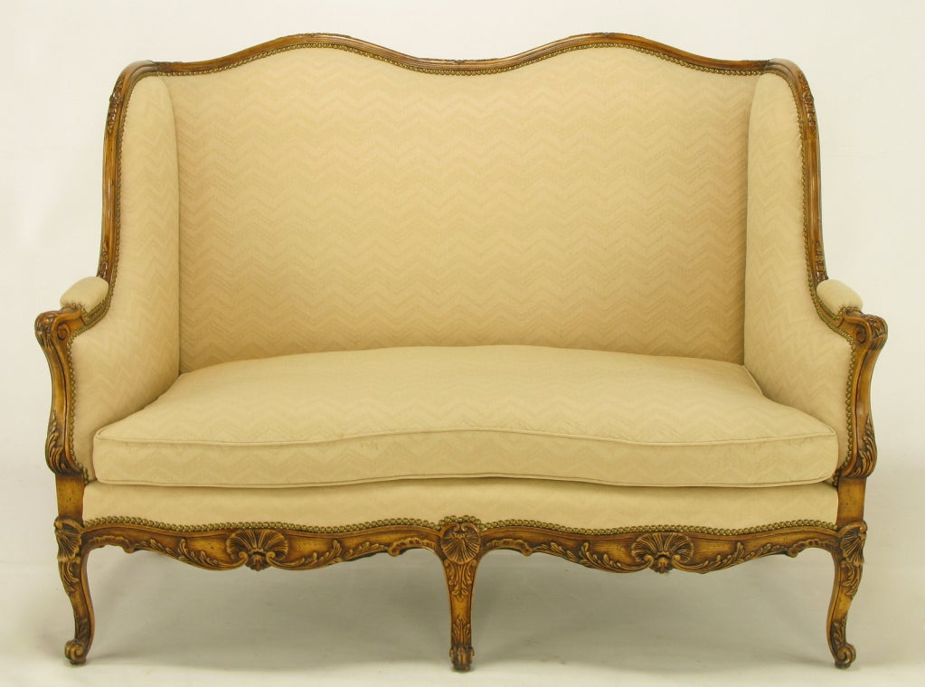 A finely crafted reproduction of an 18th century French settee, this lovely piece features an intricately carved walnut wood frame. Acanthus leaf decoration adorns the the wooden arms and cabriole legs, with carved sea shells and scroll feet adding