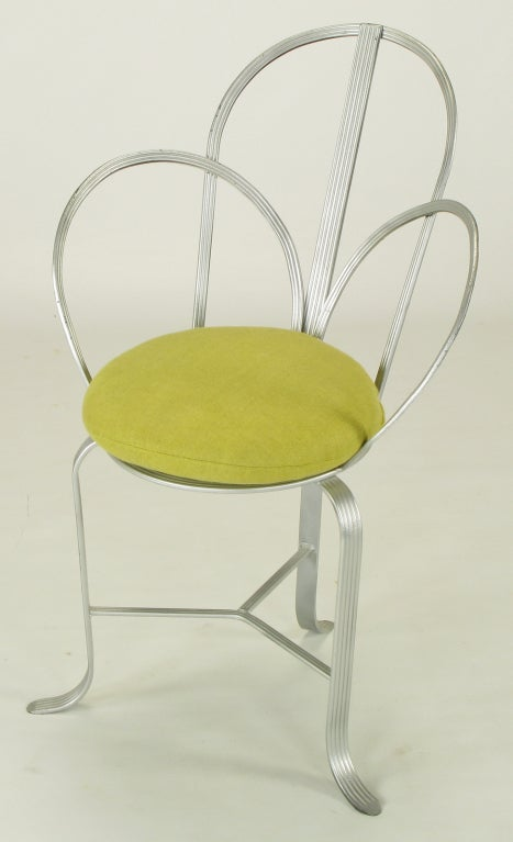 Wrought iron framed architecturally inspired chair with arched three part back and sides constructed of incised flat wrought iron bars and silver enamel. Circular seat with woven iron center, three legs with turned feet and three part stretcher.