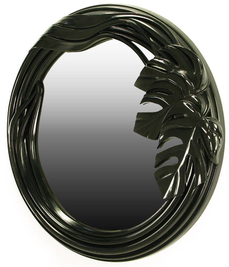 Art Deco revival mirror in cast resin with a high gloss black French polished finish. Philodendron leaf detailing with receded surround. In the style of Phyllis Morris.