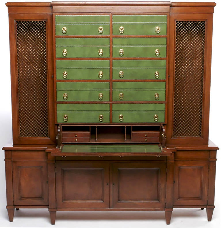 Stunning design for Johnson furniture. Green embossed leather fronts, with brass drop ring pulls, that appear to be all drawers. Starting from the bottom, the lowest pair of drawer fronts conceals a pull-out writing desk or secretary. The next pair