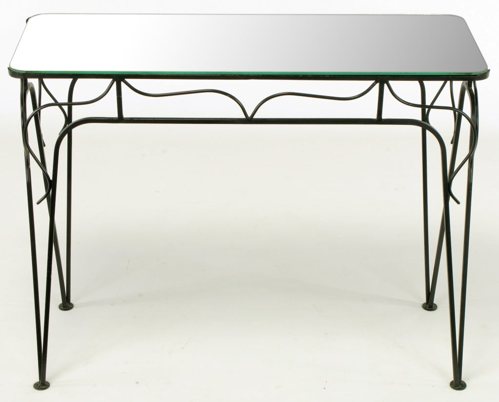 Petite console table constructed of wrought iron and lacquered matte black attributed to Mario Tempestini for Salterini. Mirrored glass top.