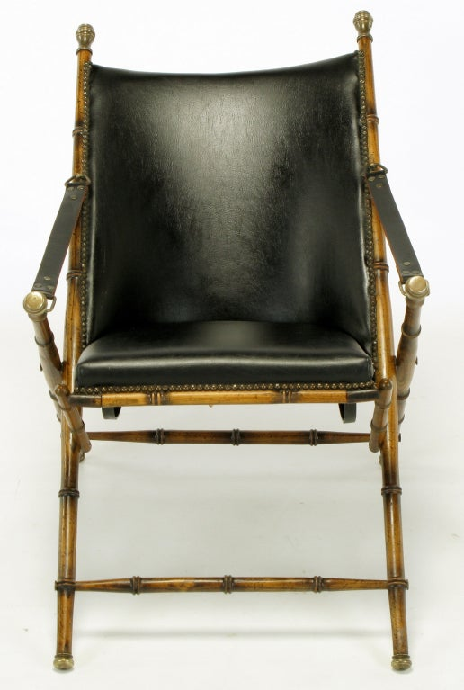 A Classic design, with folding wood frame carved to appear as bamboo, brass caps, leather seat and back with brass nailhead trim, and leather arm straps.