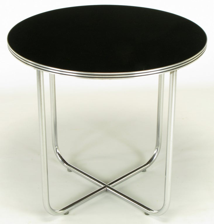 American art deco table designed by Wolfgang Hoffmann and marketed through Howell Designs of St. Charles Illinois. Chromed metal tubular U shaped legs that meet at the floor to make an X pattern. incised chrome and black lacquer edge banding. Black
