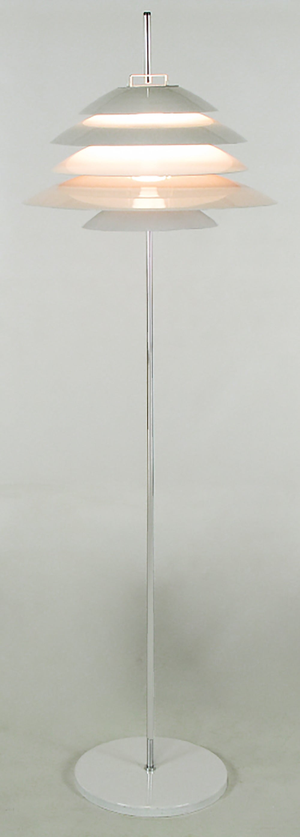 Very sculptural floor lamp by Robert Sonneman. Has layers of white metal shading to baffle the bulb, resulting in very atmospheric lighting.
