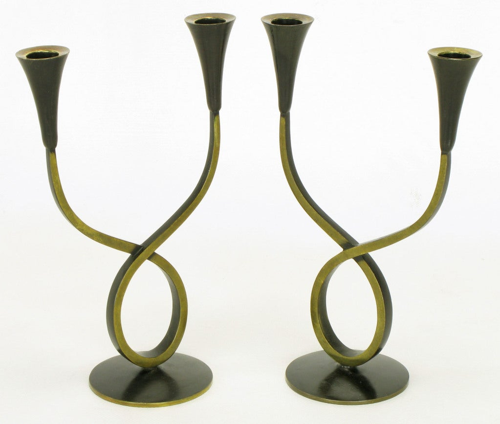 Pair of pantinated brass double arm candelabra, possibly a Hagenauer design by Rena Rosenthal, made in Austria. Patinated and lacquered brass sinuous double arms that appear to be a single arm looped at the base. Stamped