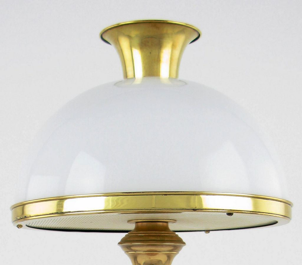 Evocative of some John Dickinson lamp designs, this table lamp has a central brass baluster form over a polished steel octagonal base.    The shade is a milk glass hemisphere, crowned by a cast brass