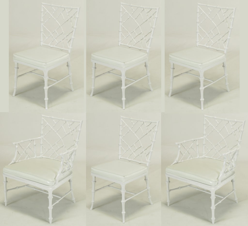 Set of six Phyllis Morris white lacquered Chinese chippendale dining chairs constructed of cast aluminum and white vinyl seats. Exaggerated faux bamboo detailing with tapered saber legs, X stretcher base and slightly off kilter backs and arms.