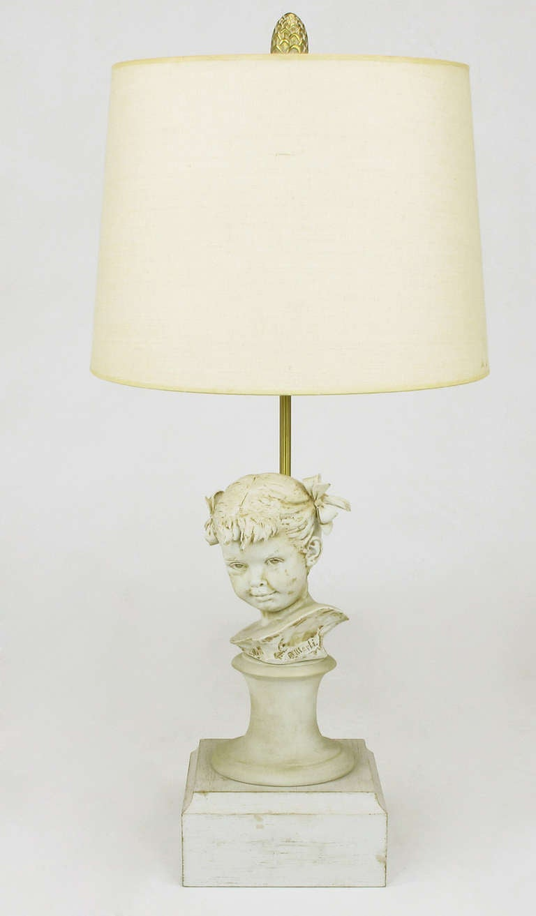 Marbro table lamp featuring a Bruno Merli, capodimonte porcelain bust of a female child on wood plinth base. Sold sans shade.