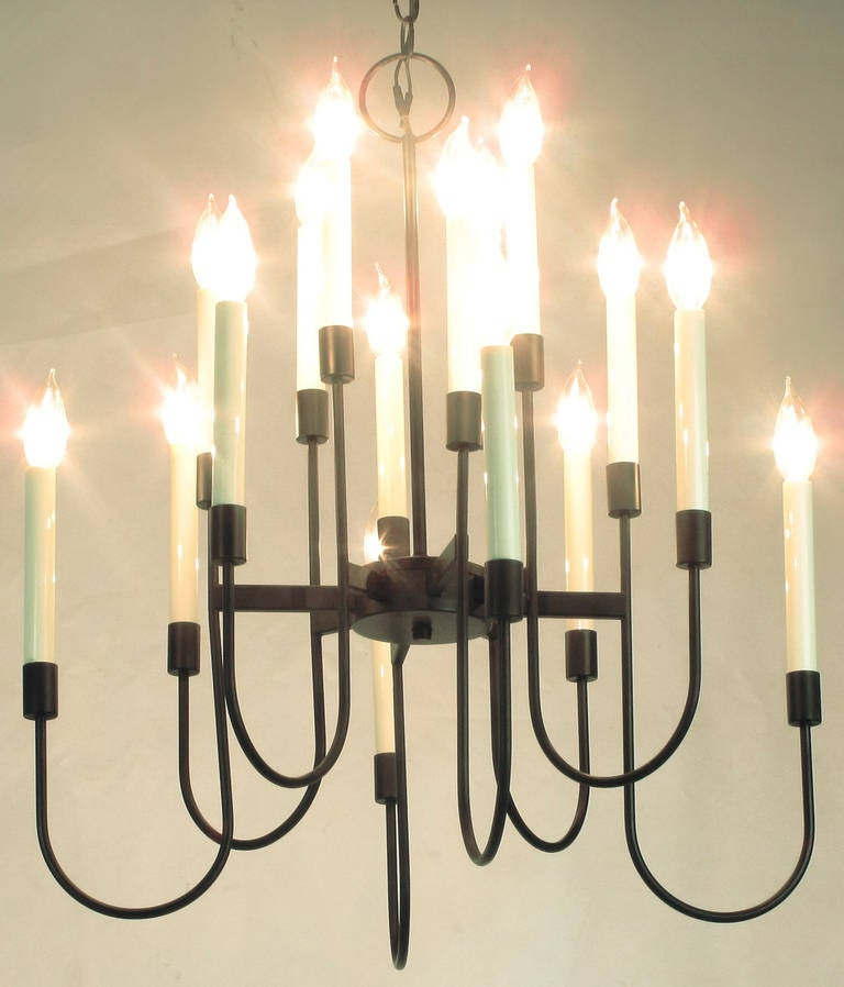 Elegant black lacquer sixteen-light chandelier by Lightolier. The design is often attributed to Tommi Parzinger. The chandelier is comprised of eight spokes radiating out from the centre disc, with each bar holding two lights on a curved rod. Comes