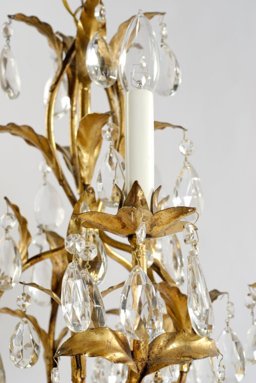 Gilded metal foliage supported by five arms with lights. Many crystal drops embellish the fixture.