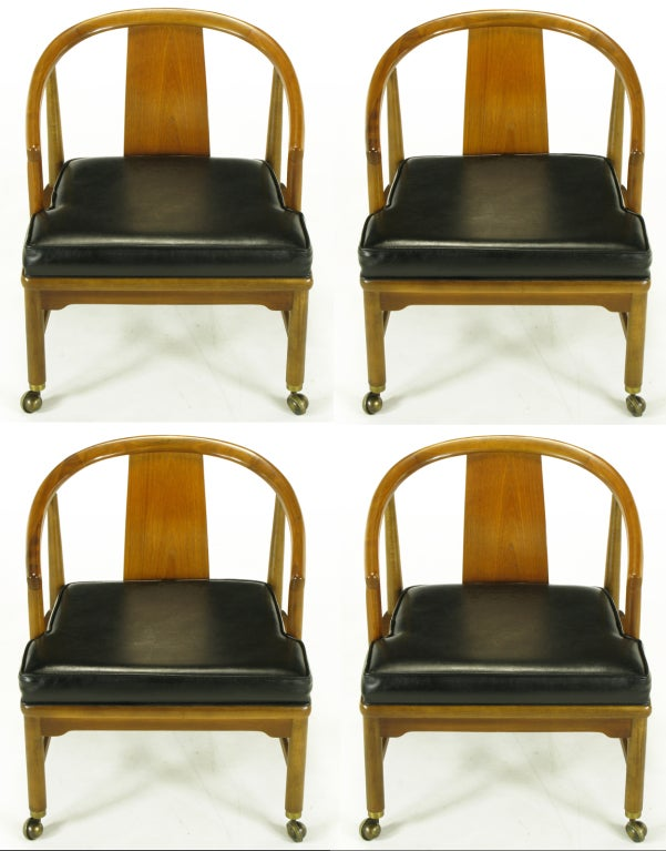 Set of four Asian inspired bent plywood back support, low slung mahogany dining chairs that could also function as uncommon game table chairs. Curved yoke back that runs seamlessly into the 3/4 length arms. Asian bracket style apron and platfoarm