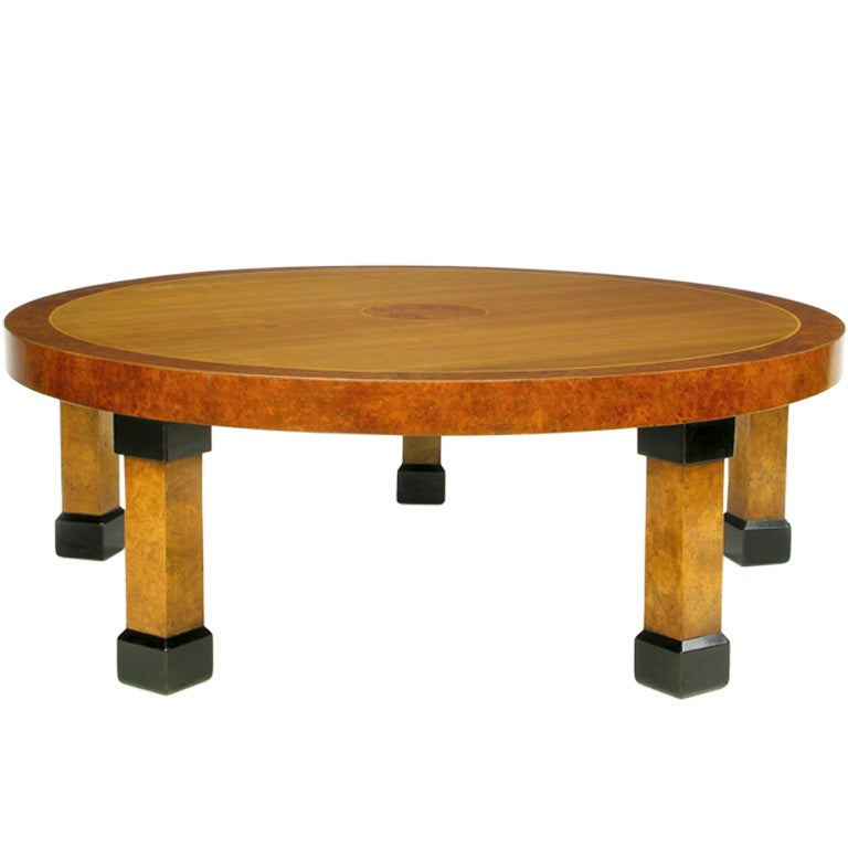 This beautifully executed round Art Deco revival coffee table by Baker Furniture features mahogany and burled woods, with square column legs. Black lacquered capitals and sabots.