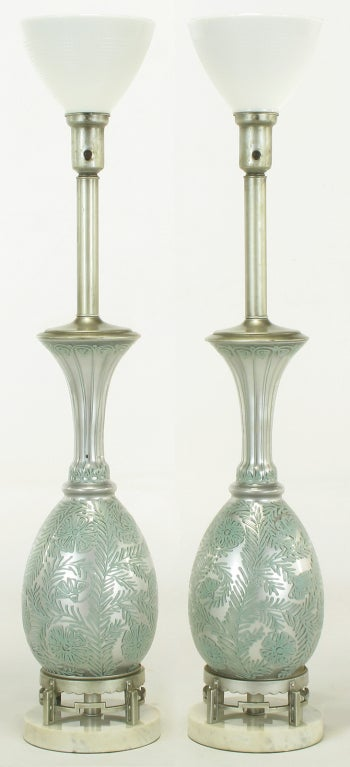 Pair of reverse silvered glass table lamps with hand-painted turquoise blue relief floral pattern. Silver lacquered cap, stem and cup with milk glass shades. Silver lacquered brass open pedestal on Carrara marble base.