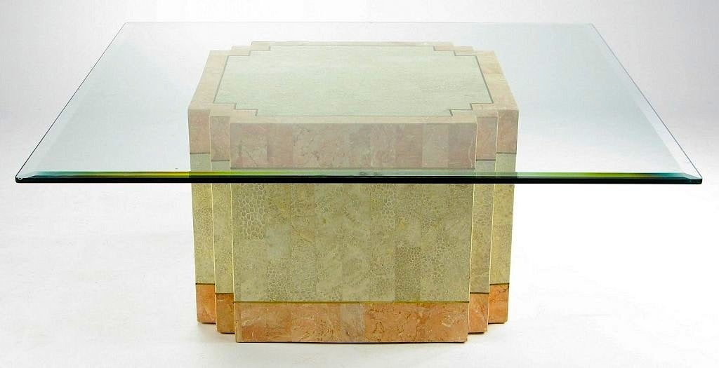 A derivation of Art Deco style, this coffee table has a square base with setback corners. The strong geometric form is accentuated by the coral color marble and fossil stone cladding, separated by solid bands of brass. Designed by Marcius for Casa