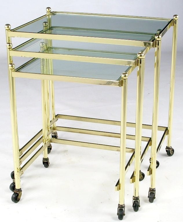 An extremely well-crafted set of three nesting tables in solid brass. The workmanship is on par with that of Maison Jansen. The brass ball finials add an elegant touch and the casters facilitate ease of movement. The clear glass is new, and a