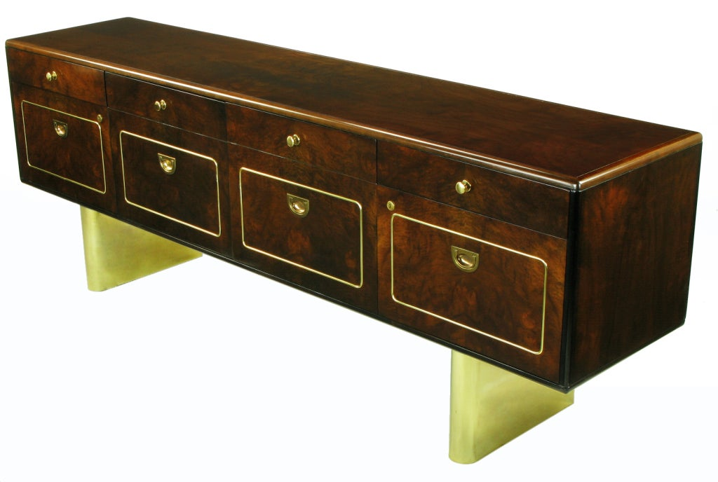 Rare Romweber Furniture dark finished burled walnut floating credenza or sideboard. Heavy brass double pedestal base, radiused front with flat back. Brass welting to the lower front file drawers and pair of doors that open via recessed U shaped