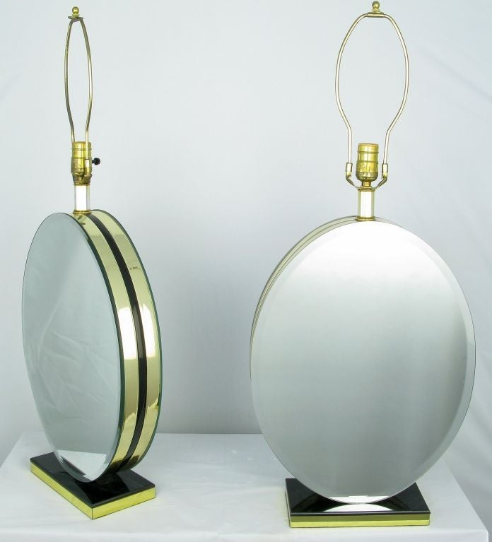 Elegant two-sided beveled mirror table lamps on a black marble and brass rectangular plinth. The mirrored bodies are comprised of black Lucite sandwiched between brass and then finished with the beveled mirror. Sold sans shades.