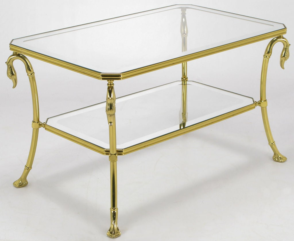 Brass two-tiered side table with four swan necks supporting the top glass tier. Lower glass tier interposed between the swan necks and the webbed feet. Canted corners and brass ribbon edged shelves. Glass surfaces bordered in mirror.