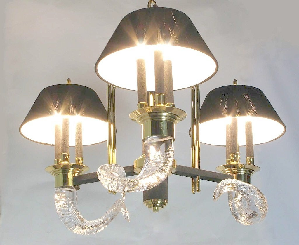 Unique and elegant, this three-arm, nine light chandelier is a 1980s deco revival piece. Crystal rams' horns, solid brass, black textured metal with three hand wrapped black wool shades, and enough brass chain to hang from a high ceiling.