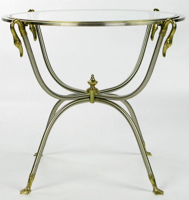 Lovely round side table with a double curule frame of nickeled steel and brass. The clear glass top is surrounded by a nickel and brass frame that is supported by four long brass swans' necks.