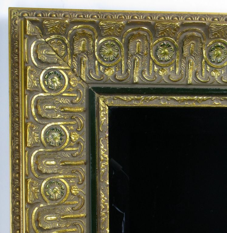 This elegant and intricately carved wall mirror is framed in deeply stepped wood and gesso, with lovely patinated gold leaf.