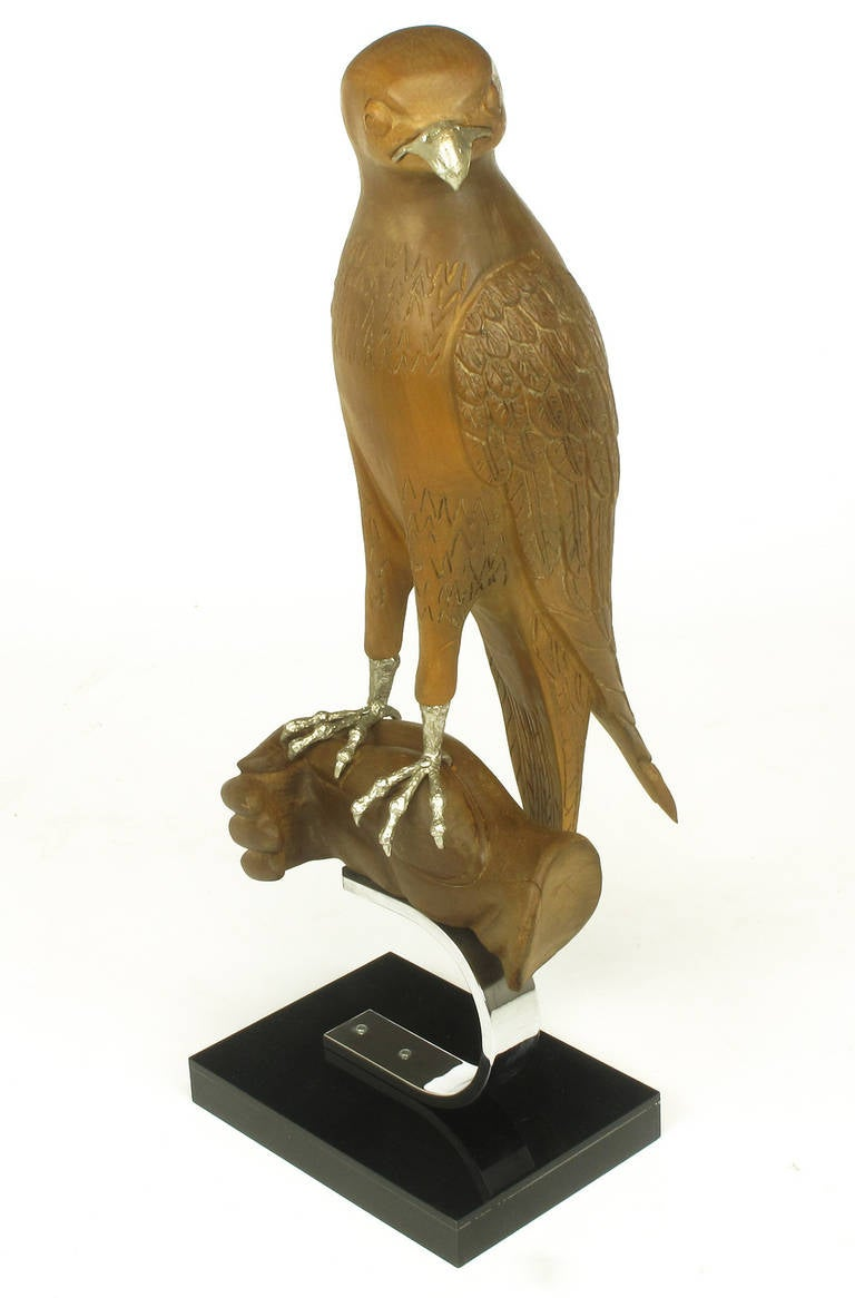 Wonderfully carved falcon or hawk, mounted on a carved wood hand. Silver talons and beak. All surmounted on a C-shaped chrome steel bracket and black acrylic over wood base.