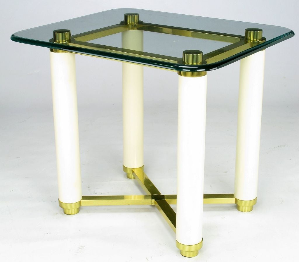 An elegant side table with solid brass caps, feet, rectangular upper stretchers, and lower X-stretcher. The legs are solid wood with fresh ivory lacquer. A very unusual piece of glass with a curved top edge is original.