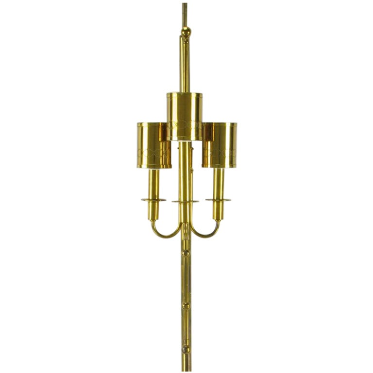 Polished brass three light tension-pole floor lamp, with mounted sconce in the manner of Tommi Parzinger. Three curved arms with elongated brass sockets with brass bobeches finishing with a pierced brass shade. Brass rod detailing finishes with