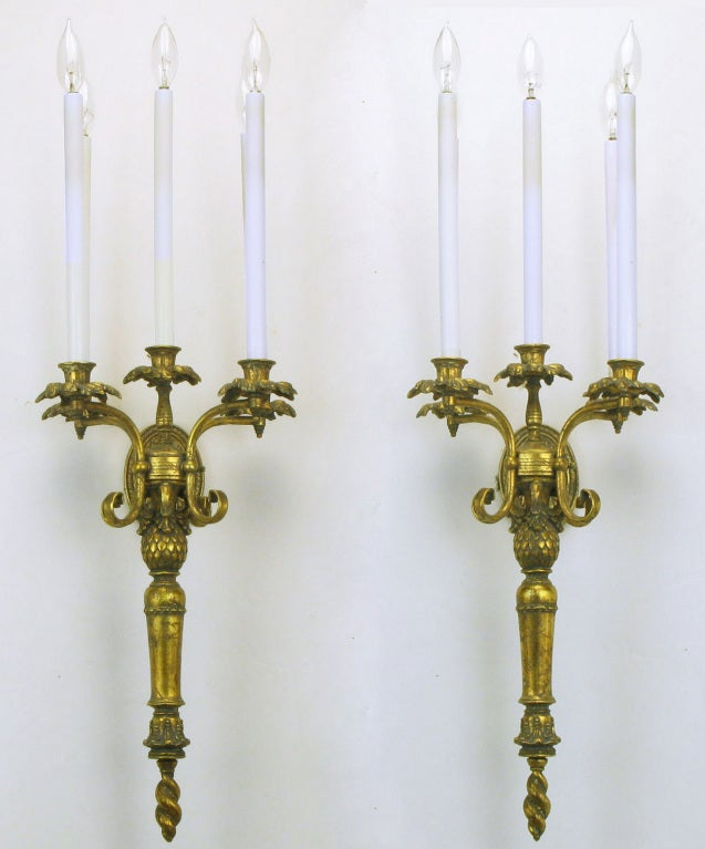 Pair of renaissance revival gilt metal five arm torchiere style sconces. Oval back plate with center arm that extends to hold the torchiere with five foliate bobeche, candle holder, elongated sockets with white candle covers. Lower stem with