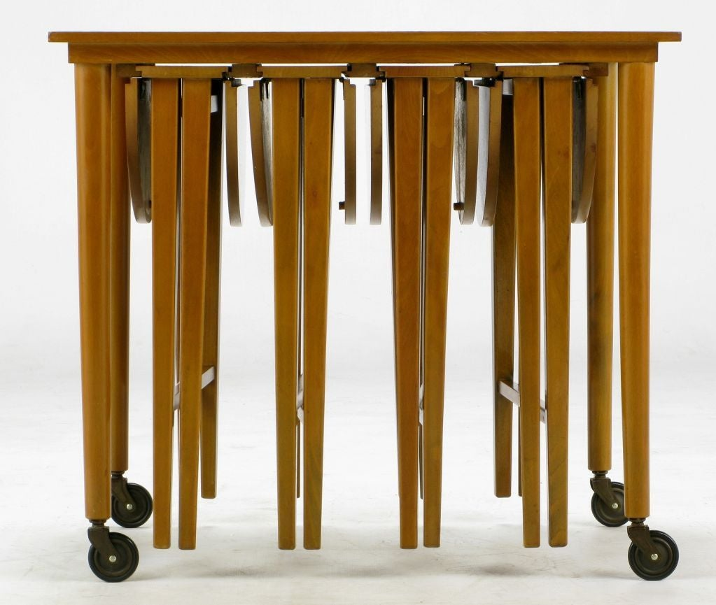 Clearly inspired by the set that Ms. Schaefer designed for M. Singer & Sons in 1952, for which she won a Good Design award. Four folding dropleaf tables slide into tracks under the top of the largest of the set, an end table, which is mounted atop