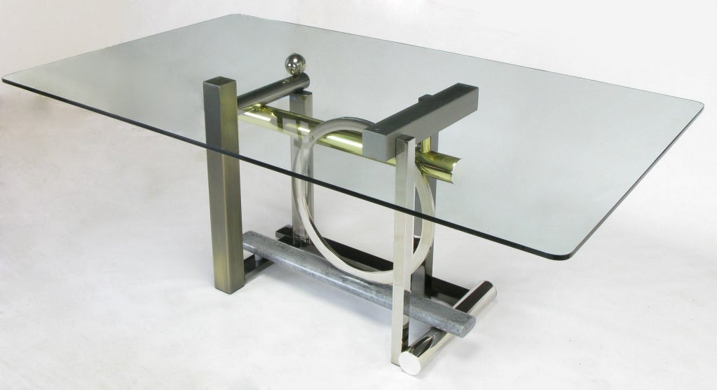 Design Institute of America Postmodern glass top dining table with geometric metal base. Base is comprised of metals in various shapes and finishes; chrome ball, ring and cylinder, brass cylinder, powder coated steel in heathered grey, stainless and
