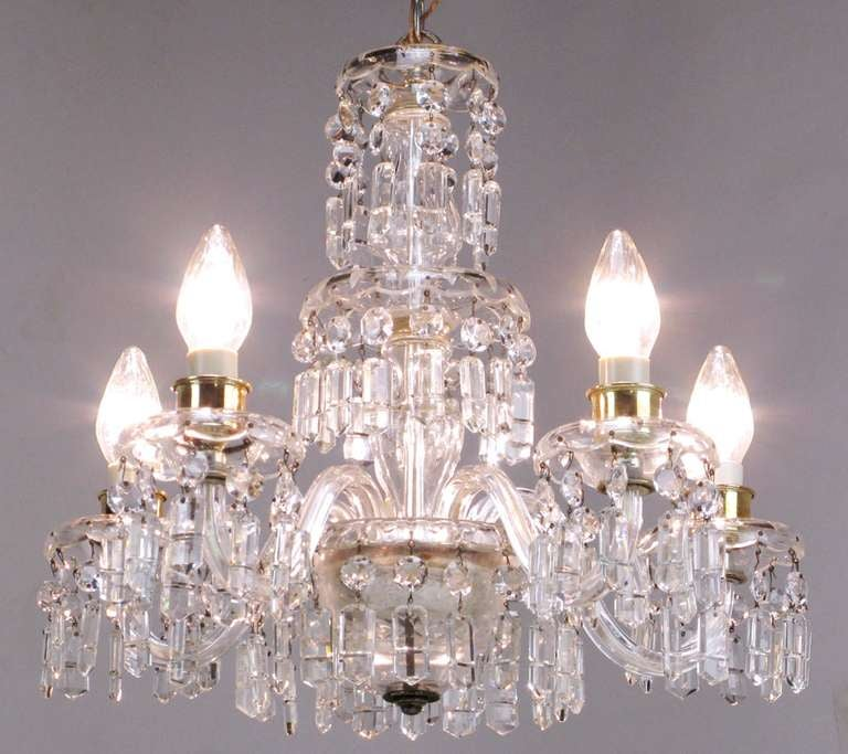 A wonderful early example of the craftsmanship of the American lighting pioneer, Lightolier. Five glass arms meet at the bottom the tri-tiered cut-glass centre column. Brass cups under the sockets can be used as fitters for hurricane shades, if