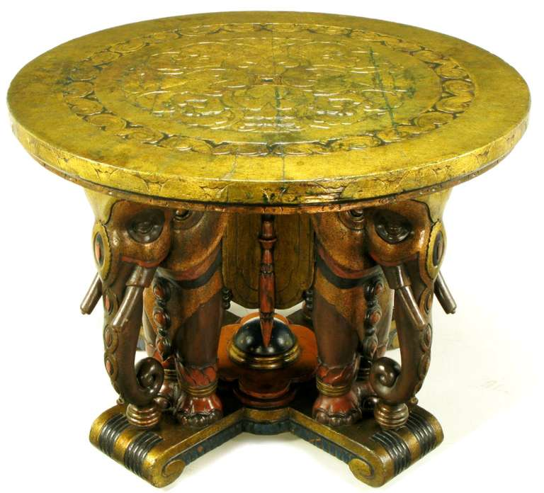 Spectacular hand-carved and parcel gilt polychrome centre table, or potential games table, with four ceremonially dressed elephants. Round gilt top carved with an art deco filigree border and a stylized quatrefoil centre. Polychrome and parcel gilt