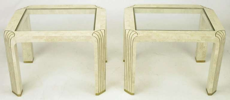 Pair of tessellated fossil stone and inlaid brass side tables. Glass tops bordered by brass trim. Canted corner legs feature brass inlaid elongated shell motif and brass sabots. Manufactured in the Philippines, as were the tessellated stone
