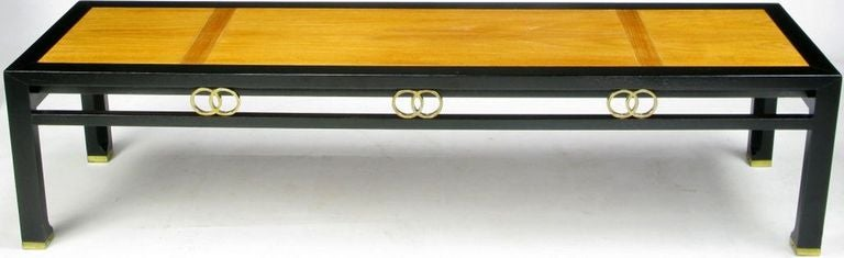 This elegant cocktail table byMichael Taylor for Baker Furniture is exquisitely detailed with interlocking brass rings and sabots. Refinished in a black lacquer frame and inlaid walnut top.
