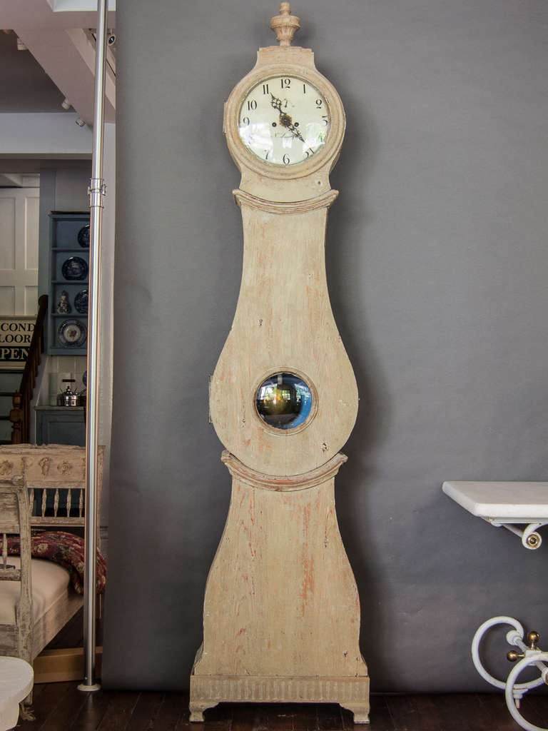 A Swedish tall case clock in the traditional Mora style. The face is signed by the maker N. Lundgren and the bonnet is topped with a carved urn. The clock has an interesting movement which includes a separate minute dial as well as an alarm, grey or