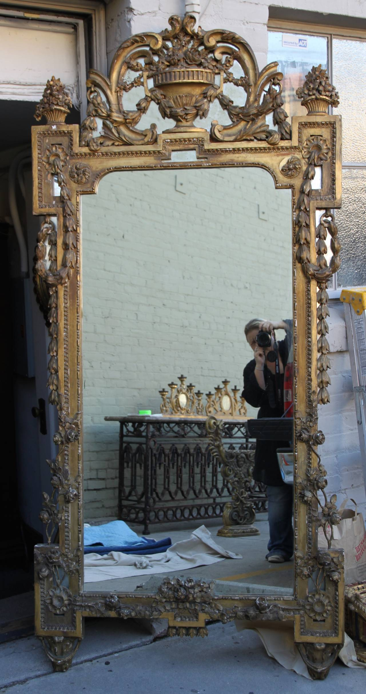 19th century Italian Baroque style giltwood carved mirror with centre urn, garlands, and acanthus leaves throughout.