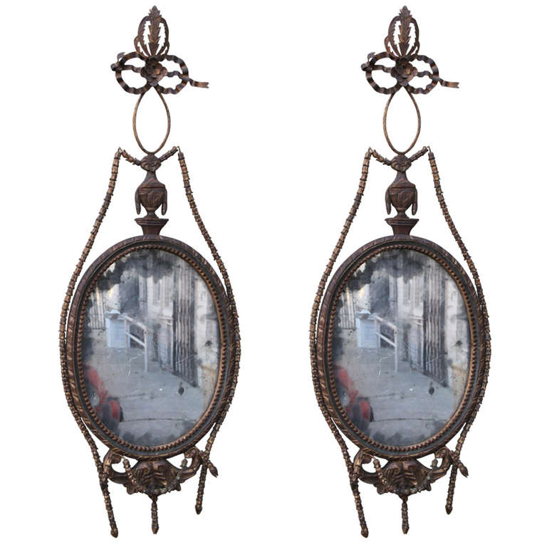 Pair of carved wood and tole mirrors with original ghost mirror inset.