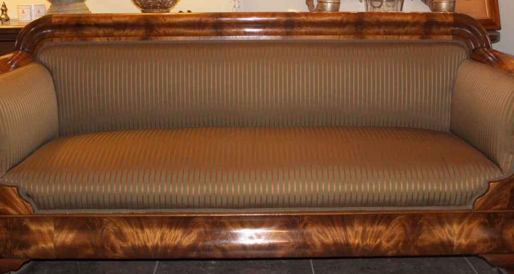 19th century Flame Mahogany veneer America Empire Sofa with new striped upholstery.