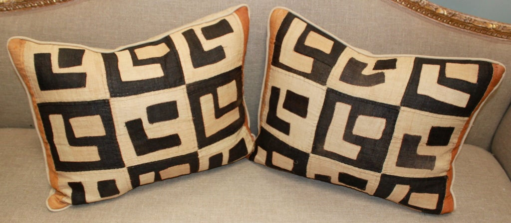 Pair of vintage Kuba Cloth pillows with linen backs and self cording. Down & feather inserts.