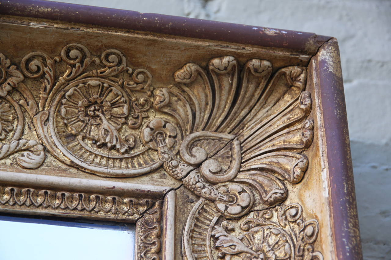 19th century Italian giltwood mirror with carved details of faces, flowers, shells and acanthus leaves throughout.