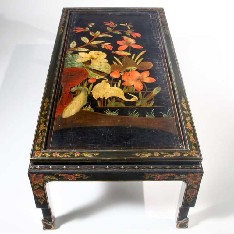 Long rectangular 18th century oriental black lacquered coffee table with large-scale bird and flower patterns. Designed using an antique painted oriental chinoiserie panel or screen that has been fitted to a custom designed base with extensive