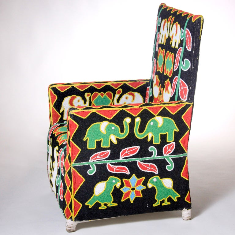 Exquisitely crafted Nigerian chair in vivid primary colors on black background.  Canvas covered wood frame chair  with extensive hand beading.  African artists used native animals (elephants, lions, rhinos and birds) juxtaposed with plant shapes and