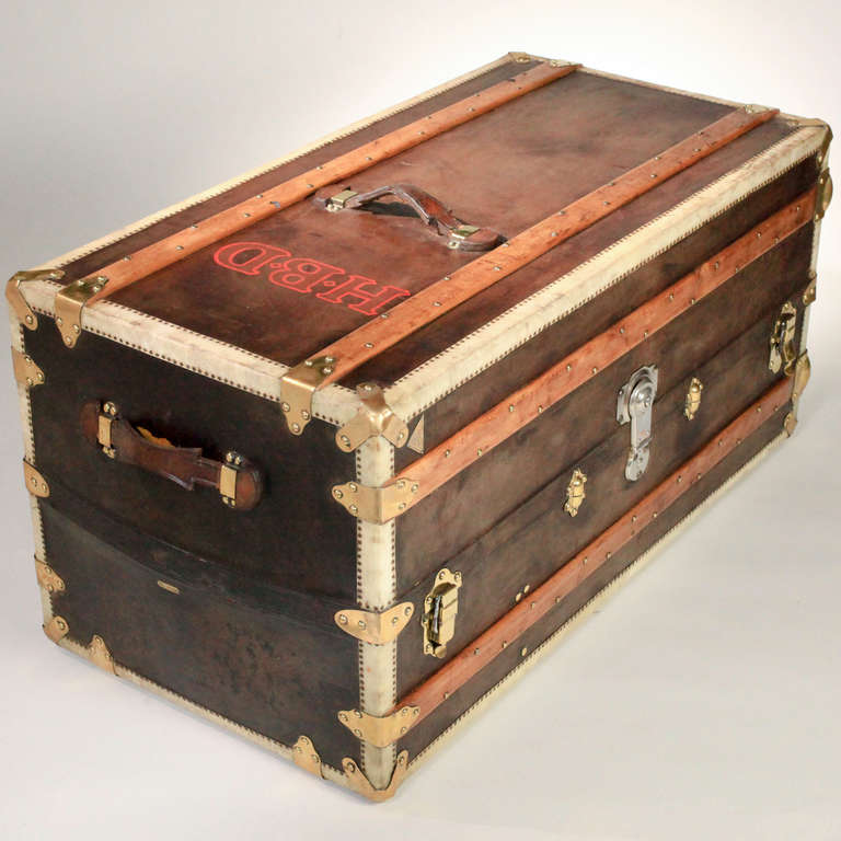 """Large vintage French leather steamer trunk with wood struts and brass appointments. The interior with original wallpaper and matching fabric. Five side drawers and hanging wardrobe section. The brass corners stamped """"L G depose Paris;"""""""